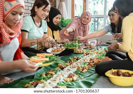 muslim asian woman social gathering at home having lunch together. javanese traditional cuisine #1701300637