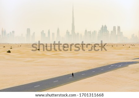 View from above, stunning aerial view of an unidentified person walking on a deserted road covered by sand dunes with the Dubai Skyline in the background. Dubai, United Arab Emirates. #1701311668