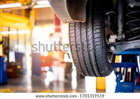 car automobile mechanic working on repairing the wheel tire of vehicle, taking car in for service workshop for male car mechanic fixing problems replacing broken parts of using tools and equipment #1701319519