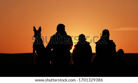 Happy family on sunset background, silhouettes of people and dogs, beagle and belgian shepherd malinois.