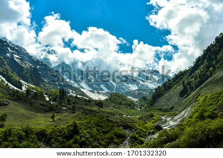 Beas Kund is situated at 12,140 ft. Above sea level in Kullu valley. Grasslands and snow-covered mountains of Pir Panjal range envelop this glacial lake. The trek starts from Dhundi (21kms from Manali Royalty-Free Stock Photo #1701332320