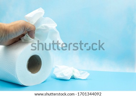 Toilet tissue paper with hand on blue background #1701344092