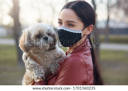 Outdoor picture of delighted lovely young female wearing antibacterial mask to protect from coronavirus, holding white Maltese dog in hands, having walk, being animal lover. Quarantine concept.