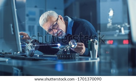 Portrait of Focused Middle Aged Engineer in Glasses Working with High Precision Laser Equipment, Using Lenses and Testing Optics for Accuracy Required Electronics #1701370090