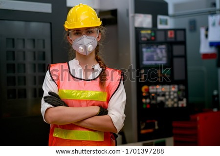 Pretty technician or worker or engineer woman with gray mask stand with confident action in workplace with concept collaboration during concern about public health of corona virus pandemic in people. #1701397288