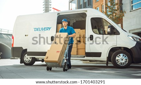 Delivery Man Pushes Hand Truck Trolley Full of Cardboard Boxes Hands Package to a Customer. Courier Delivers Parcel to Man in Business District. Royalty-Free Stock Photo #1701403291