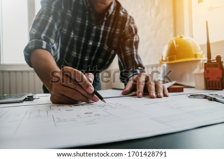 Male architect or engineer working at home drawing the construction project. Royalty-Free Stock Photo #1701428791