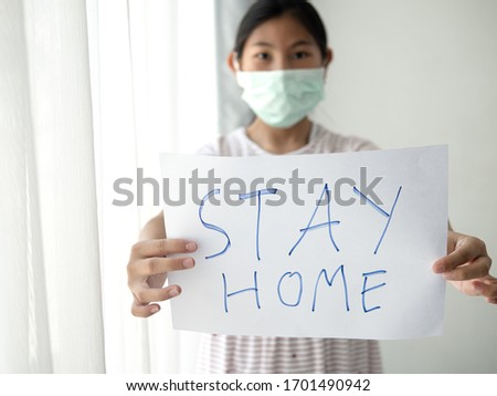 Asisan girl wearing mask holding paper message STAY HOME, during COVID-19. #1701490942