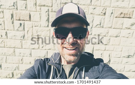 Man in sunglasses and a baseball cap listens to music on headphones and doing a selfie - Strong sunlight - Wide angle lens #1701491437