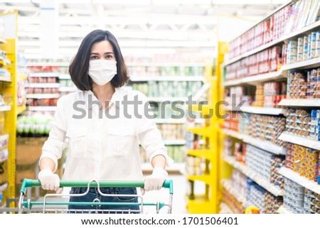 Asian woman wearing face mask and rubber glove push shopping cart in suppermarket departmentstore. Girl hold smartphone choose & look grocery things to buy during coronavirus crisis, covid19 outbreak. #1701506401