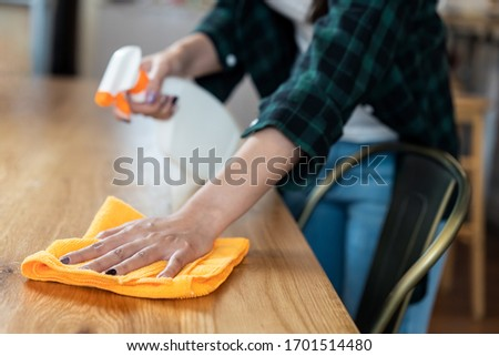 Close up view of happy woman clean home or restaurant. She wiping dust using spray and orange fabric cleaning on dirty table. House keeping maid cleaning service job to prevent covid19 virus outbreak. #1701514480