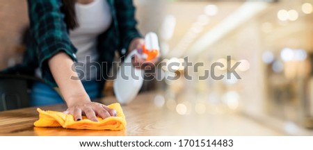 Close up view of happy woman clean home or restaurant. She wiping dust using spray and orange fabric cleaning on dirty table. House keeping maid cleaning service job to prevent covid19 virus outbreak. #1701514483