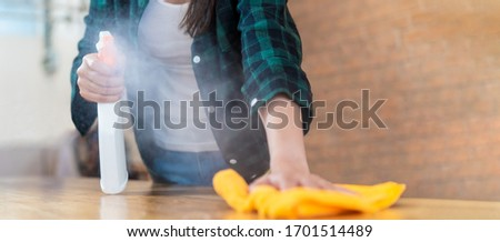 Close up view of happy woman clean home or restaurant. She wiping dust using spray and orange fabric cleaning on dirty table. House keeping maid cleaning service job to prevent covid19 virus outbreak. #1701514489