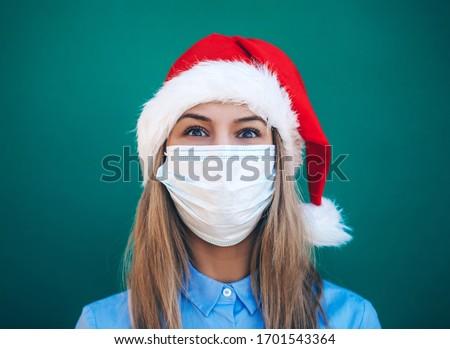 Beautiful female model wear santa hat. Christmas and New Year gifts. Mask. Celebration. Emotion. Model. Background. Santa hat. Beauty photo. Holidays. Portrait.