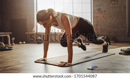 Beautiful and Young Girl Doing Running Plank on Her Fitness Mat. Athletic Woman Does Mountain Climber Workout in Stylish Hardcore Gym #1701544087