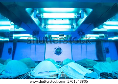 UV light sterilization of face mask to disinfect and reuse. COVID-19 prevention concept. Close up at the lamp. Royalty-Free Stock Photo #1701548905