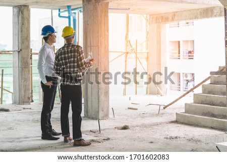 Asian contractor and engineer inspecting material in construction building. Royalty-Free Stock Photo #1701602083