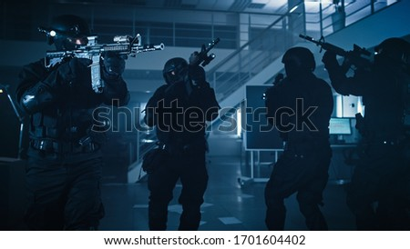 Masked Squad of Armed SWAT Police Officers Storm a Dark Seized Office Building with Desks and Computers. Soldiers with Rifles and Flashlights Move Forward and Cover Surroundings. #1701604402
