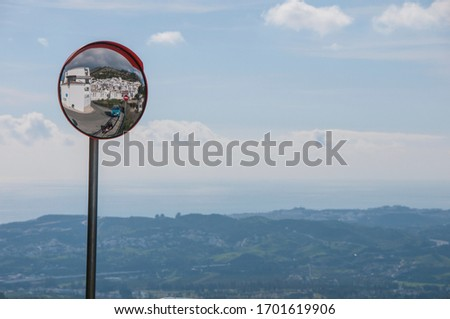 White spanish houses, road and cars reflected in a road mirror on a background of a blue sky and sea. White spanish village on a hill. Mediterranean architecture. #1701619906