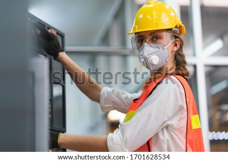 Female Engineer wear face mask with safety vest and yellow helmet operating control CNC Machinery at factory Industrial Royalty-Free Stock Photo #1701628534