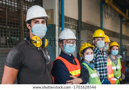 Group of diverse team of workers wearing face mask and protective helmets standing in front of the factory #1701628546