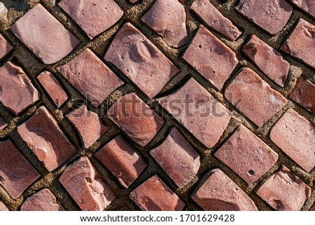 Brown rectangular stones in a mosaic on the wall close up.Abstract texture,creative background,selective focus #1701629428
