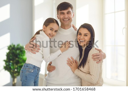 Happy smiling family. Daughter mother and father smiling hugging cheerful in a room at home. #1701658468