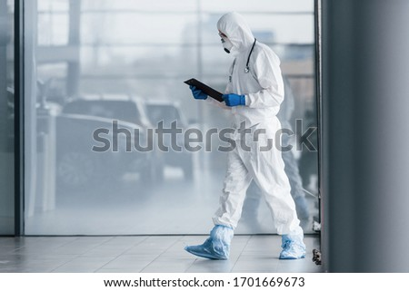 Male doctor scientist in lab coat, defensive eyewear and mask holding notepad in hands. #1701669673