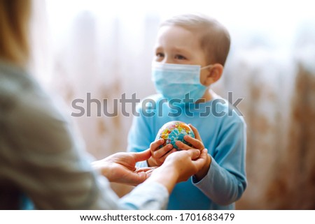 Child in protective sterile medical mask with mother holding a world globe. Save planet. The concept of preventing the spread of the epidemic coronavirus. #1701683479