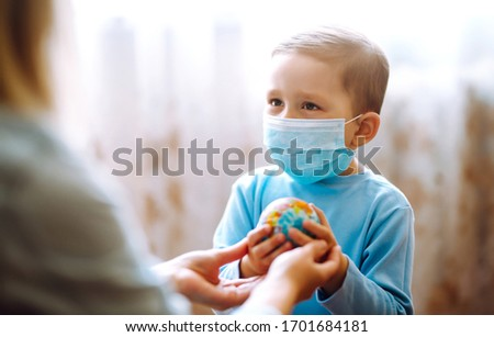 Child in protective sterile medical mask with mother holding a world globe. Save planet. The concept of preventing the spread of the epidemic coronavirus. #1701684181