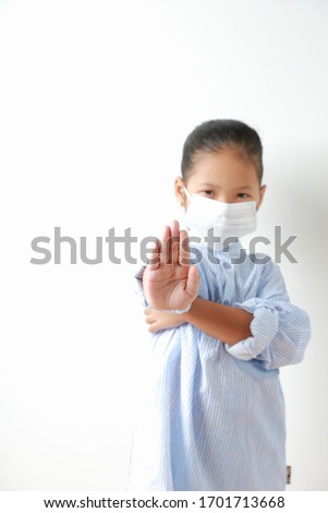 """Kid girl wearing mask for protect dust pm 2.5, virus and bacteria. Protection from sprayed saliva from patients. Show the right hand as the """"Don't"""" symbol. #1701713668"""