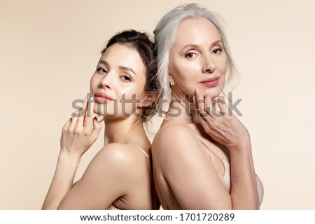 Elderly and young women with smooth skin and natural makeup standing back-to-back. Thinking, planning, dreaming #1701720289
