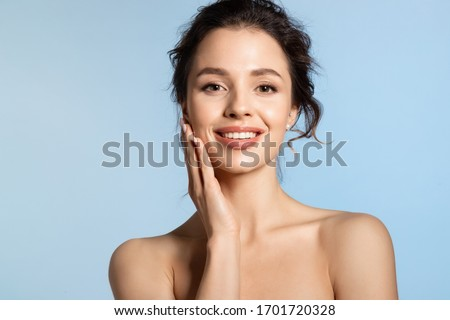 Young woman  enjoy smooth skin and touching cheek with hand. Attractive brunette girl with charming smile on face beauty studio portrait on blue background.  #1701720328