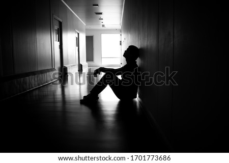 Silhouette of depressed man sitting on walkway of residence building. Sad man, Cry, drama, lonely and unhappy concept. #1701773686