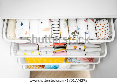 Set of baby bodysuits for a newborn girl and boy on hangers in white wardrobe. Motherhood, cleaning home kids wardrobe. Minimal fashion concept. Royalty-Free Stock Photo #1701774295
