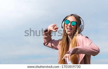 Young caucasian girl enjoys listening to music jumping for joy in a park in the city. #1701819730