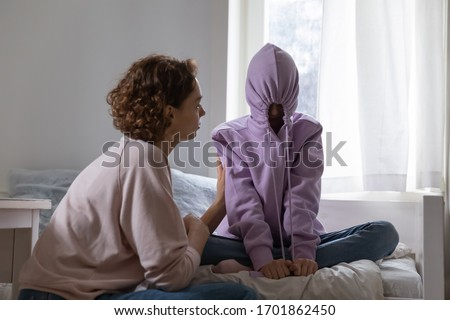 Stubborn teenage girl puts hood on head avoiding mom apology, ignoring talk with parent sitting on bed at home. Naughty teen daughter introvert hiding in hoodie showing disrespect to mother at home. #1701862450