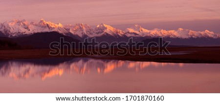 Alaska Coastal Mountain Range Reflection - The coastal mountain range across the Lynn Canal with alpenglow at sunset is reflected in a pool of water in the Chillkat Valley. Haines, Alaska. #1701870160