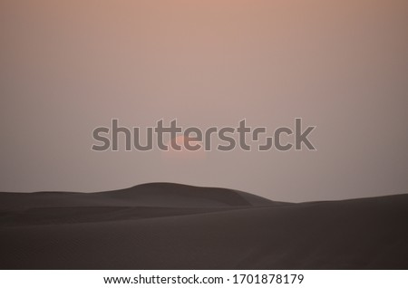 Sunset on Dubai sand dunes with picture of moonlight