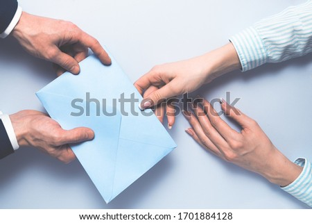 Businessman gives or takes envelope with money to woman partner. Bribery and corruption concept, salary in an envelope, money as a gift in envelope. #1701884128