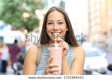 Front view portrait of a happy girl looking camera drinking milkshake in the street #1701884653