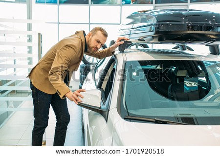 young handsome caucasian guy examining new car before making purchase. perfect auto in dealership. man want to buy it #1701920518