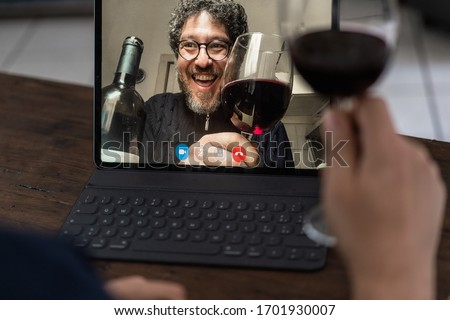 Two middle aged friends toasting with red wine in video calling  Royalty-Free Stock Photo #1701930007