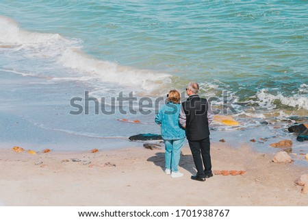Middle aged couple in sunglasses stands near ocean and looks left. Woman in jeans jacket and pants. Adult pair enjoying waves in sea. Get some fresh air on a seashore. Walk. Sand beach. Walking #1701938767