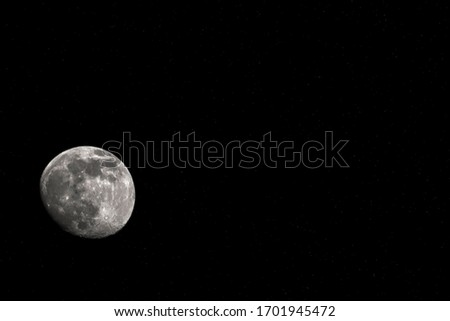 The moon is the only satellite of the Earth against the black sky. A real photo with space for the caption.