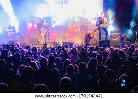 Silhouettes of people enjoying live concert of musician band performing song on stage in bright spotlights Royalty-Free Stock Photo #1701946441
