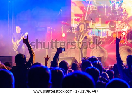 Silhouettes of people enjoying live concert of musician band performing song on stage in bright spotlights Royalty-Free Stock Photo #1701946447