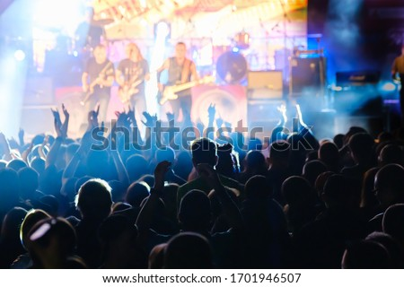 Fans at live rock music concert cheering musicians on stage, back view Royalty-Free Stock Photo #1701946507