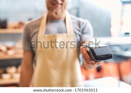 Young bearded man wearing eyeglasses and apron assistant standing at bakery shop small business giving card reader machine to customer taking payment close-up blurred background smiling cheerful