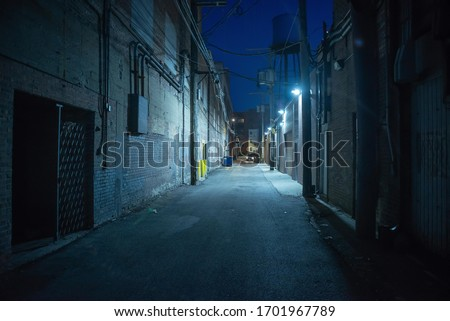 Dark and eerie urban city alley at night Royalty-Free Stock Photo #1701967789